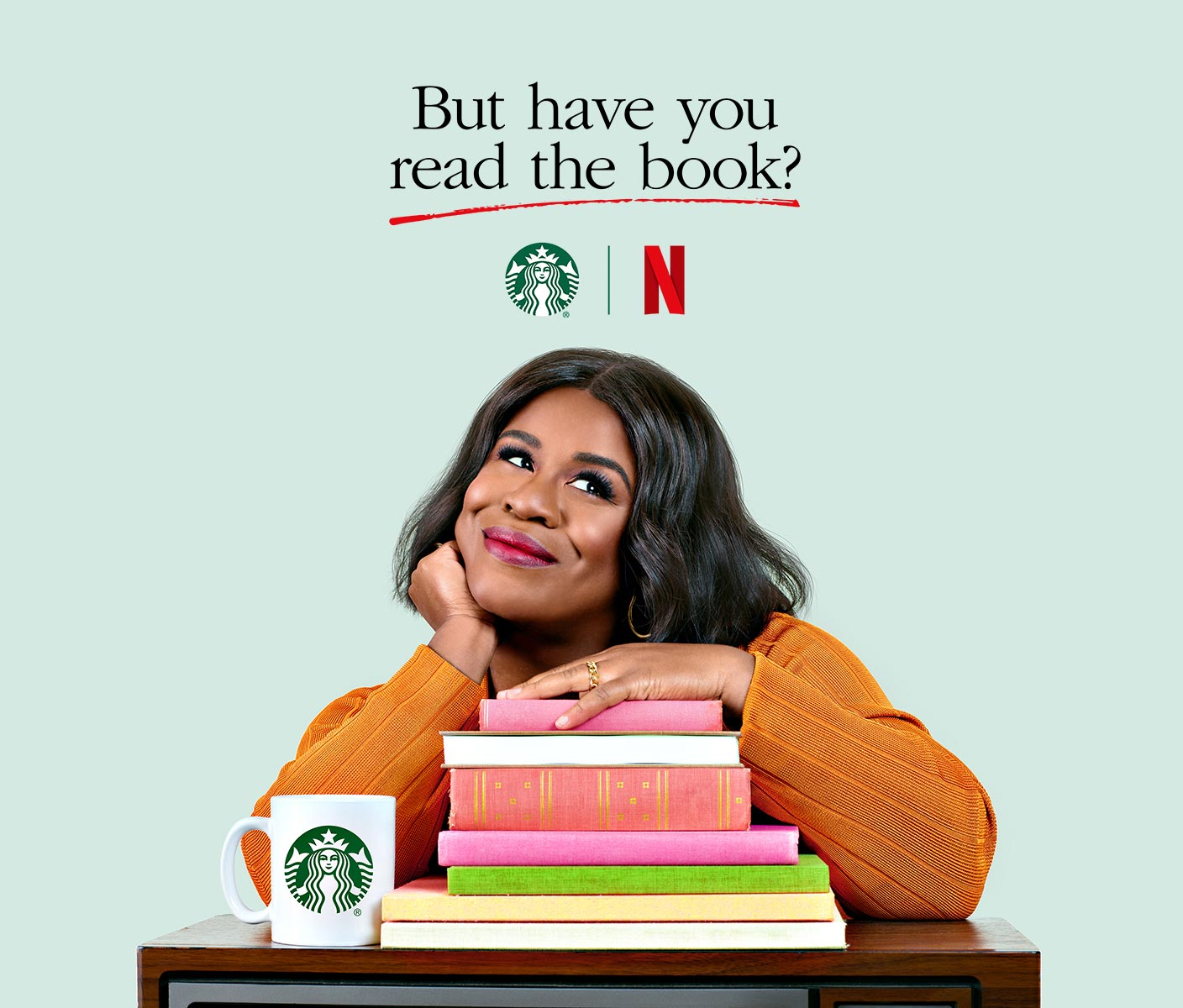 Actress Uzo Aduba poses with a pile of books, a TV and a Starbucks mug to promote a new series named But Have You Read the Book.