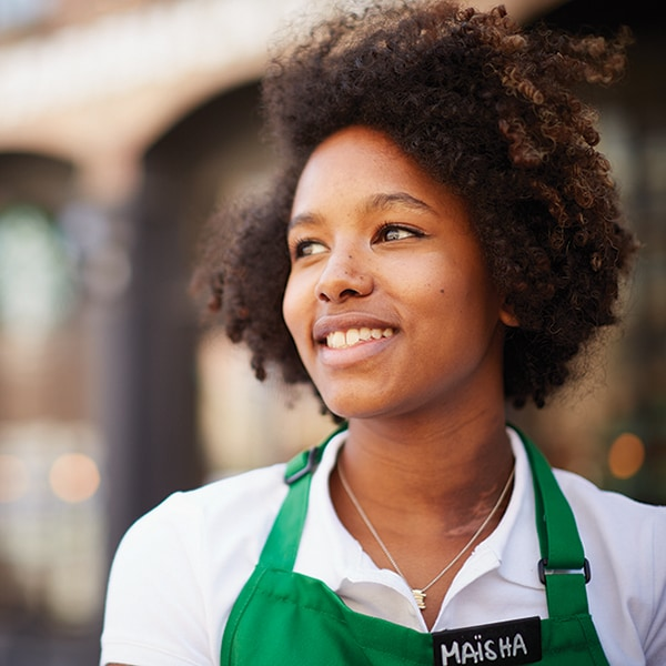 diverse female employee, wearing green apron, standing outside a Starbucks store