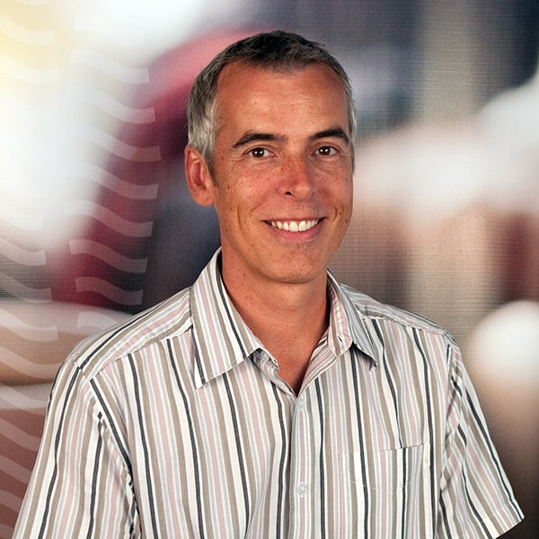 Smiling photo of a male employee, with gray hair, wearing a striped shirt