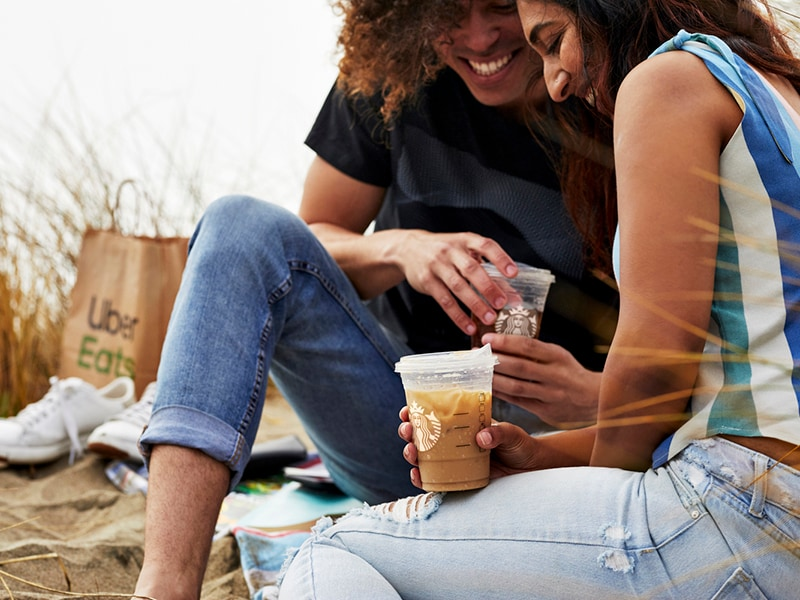 Smiling couple enjoying Starbucks beverage on beach with Uber Eats bag in background.