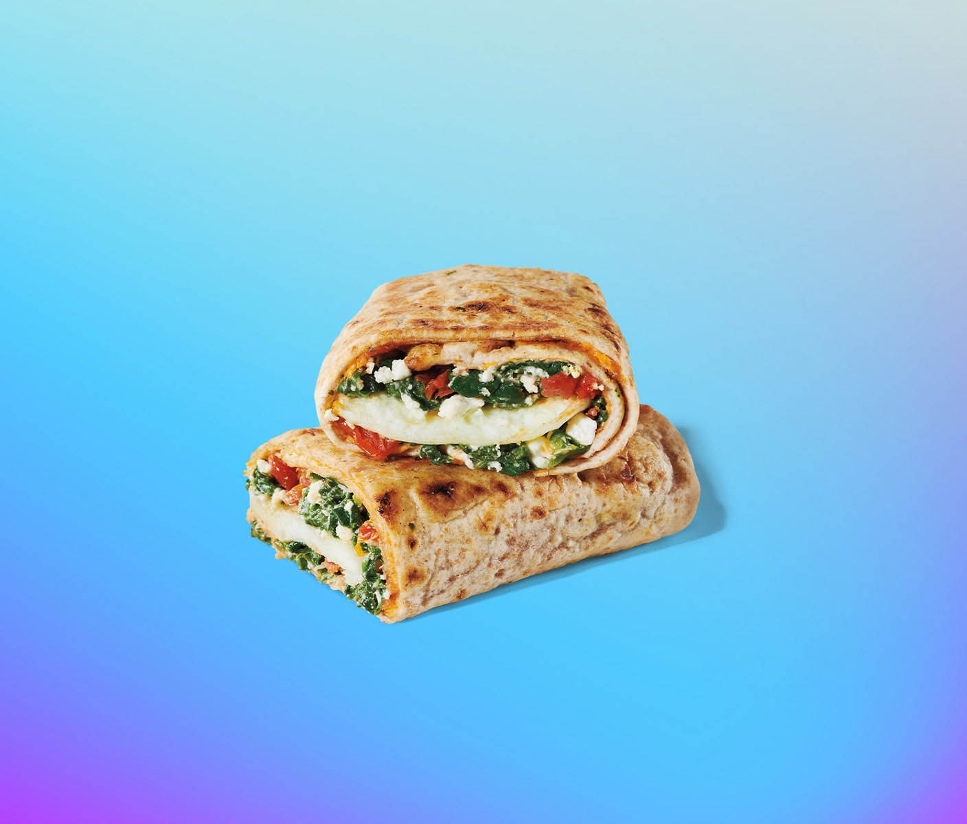 Breakfast wrap cut in half to reveal savoury ingredients