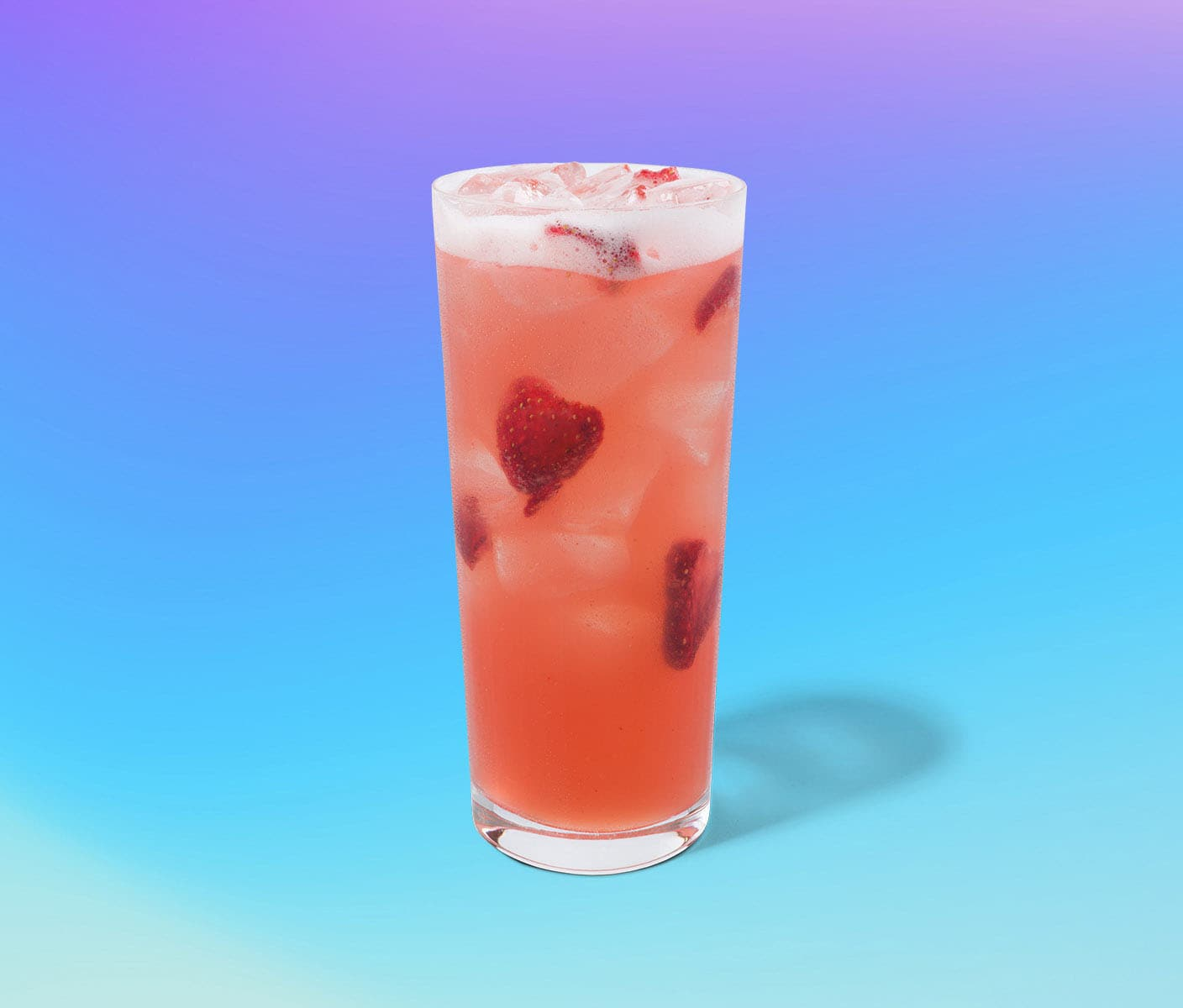 Iced drink in tall glass with strawberry inclusions