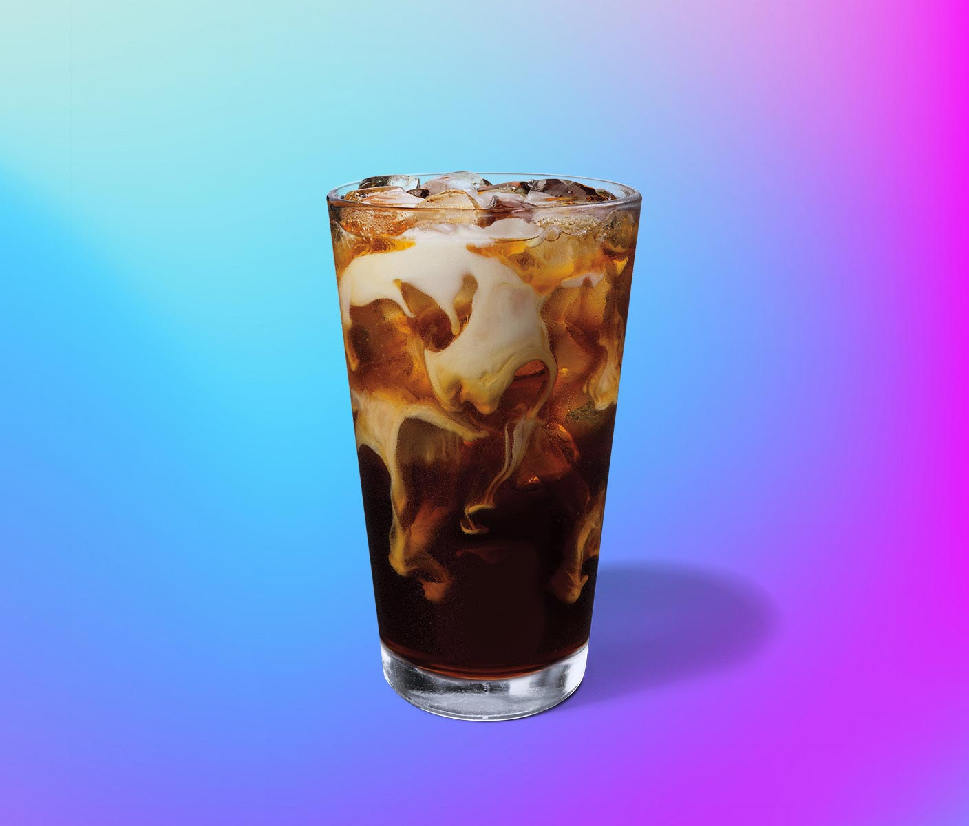 Cold coffee drink with swirls of cream in a clear glass
