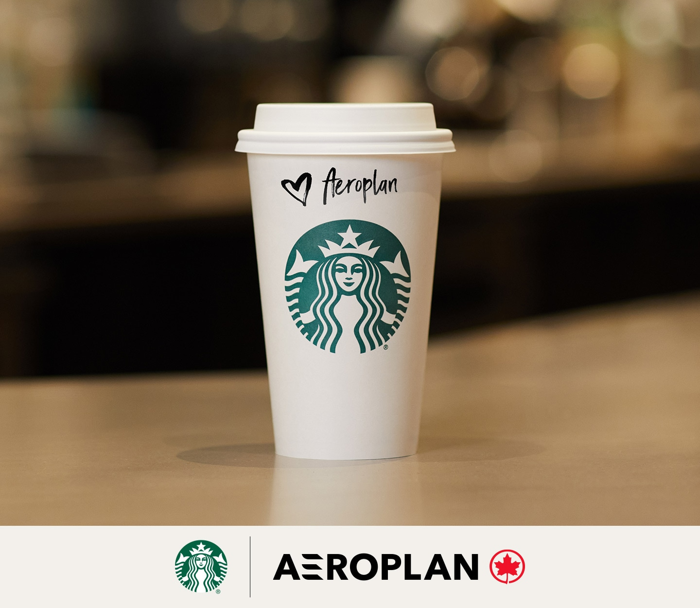A tall Starbucks hot cup with lid sits on the bar of a café waiting to be picked up. The customer name on the cup is Aeroplan.