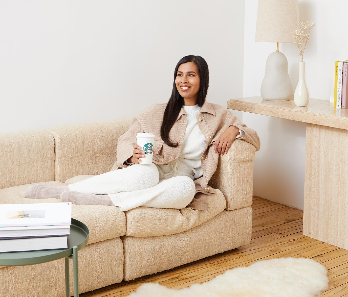 A young woman sits on the couch in her warm, brightly lit home holding her Starbucks to go order and smiling optimistically.