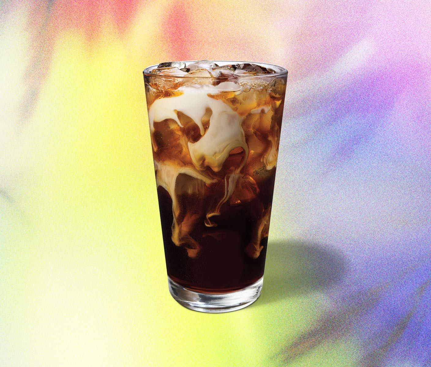Swirls of iced coffee and cream in a glass.
