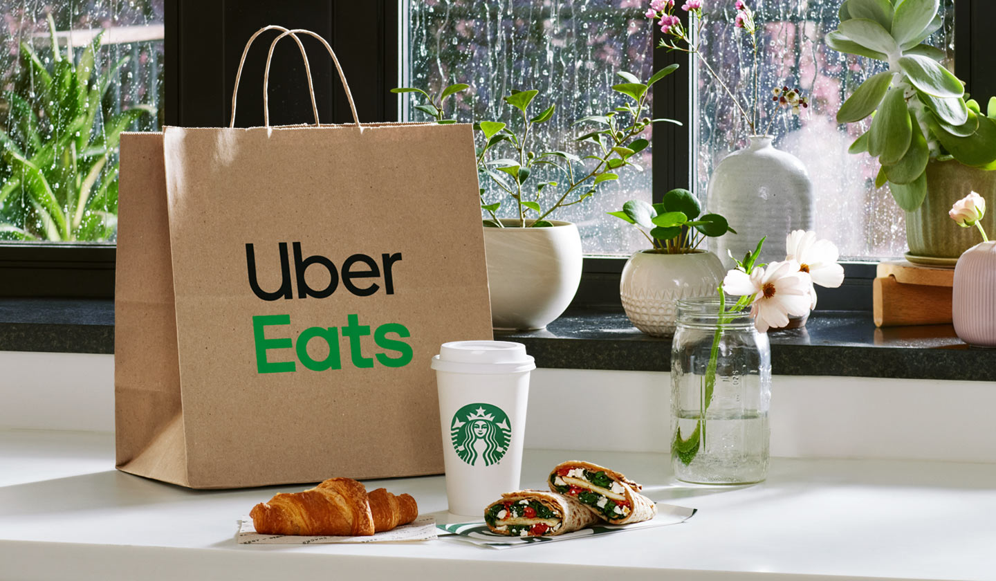 An Uber Eats delivery bag and assortment of Starbucks coffee and bakery items on a counter