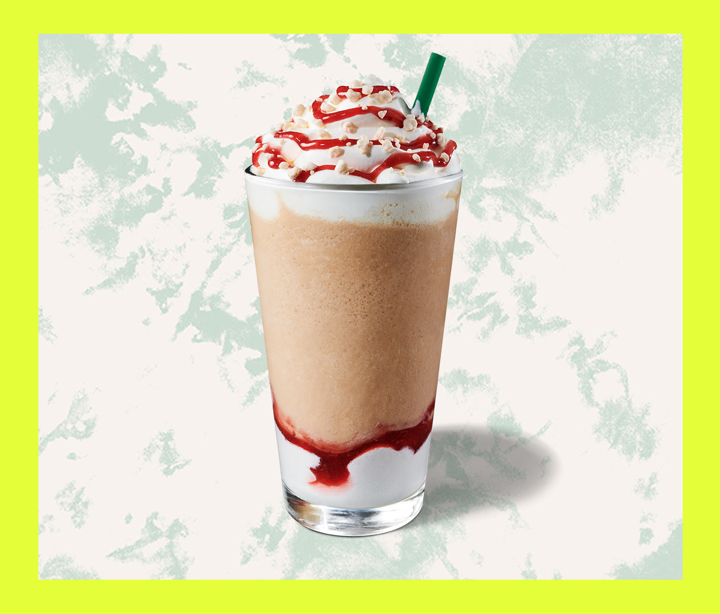 Blended coffee drink with whip cream and strawberry topping in a tall glass.