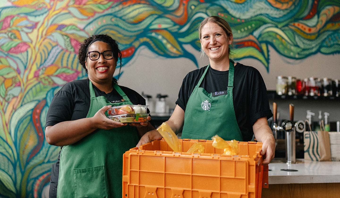 Two Starbucks employees in a Starbucks store smile for the camera while displaying a yellow crate of packaged food.