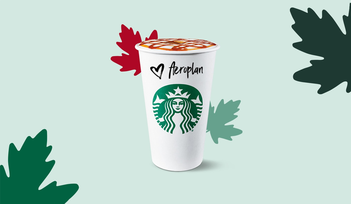 A Starbucks hot cup with  Aeroplan written on it surrounded by colourful fall leaves.