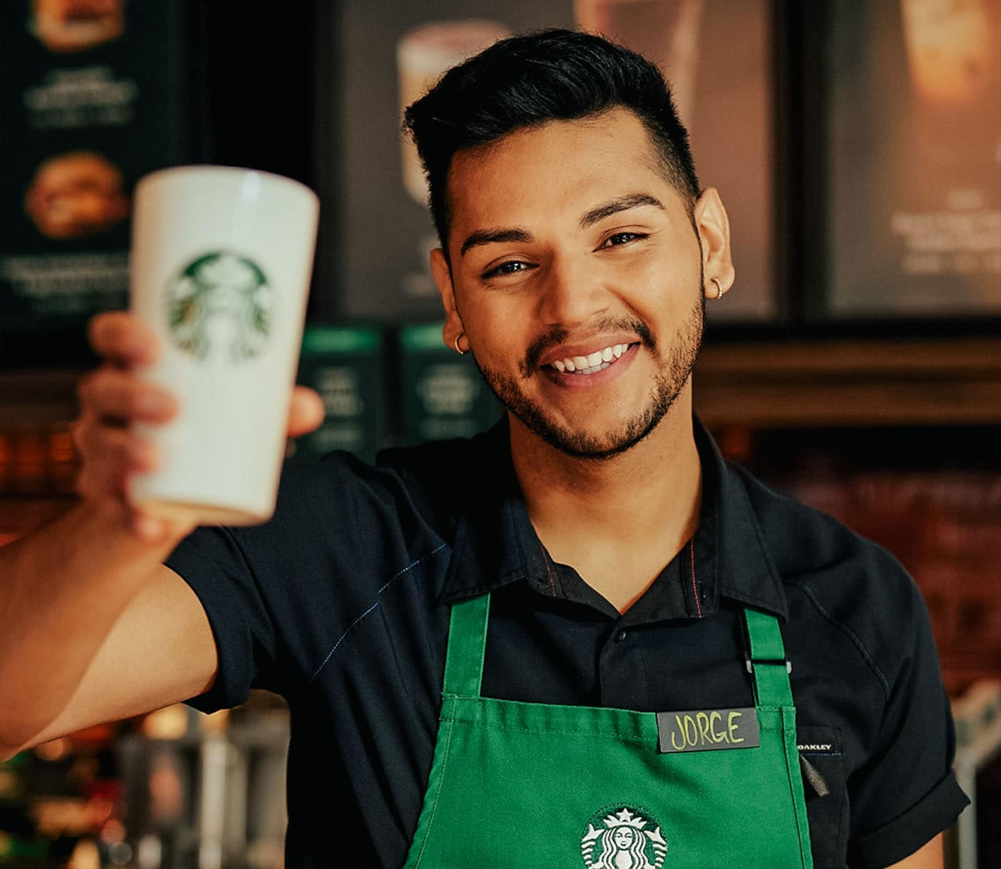 Starbucks barista in a green apron holds up a to-go cup while smiling at the camera.