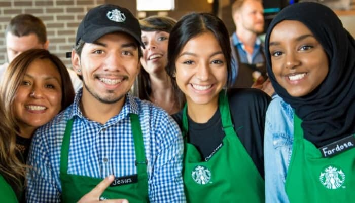 Group of baristas wearing green aprons