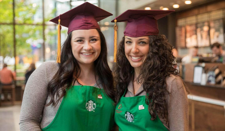 Deux femmes dans un magasin Starbucks sourient pour la caméra. Elles portent le tablier vert ainsi qu'un chapeau de remise des diplômes rouge bordeaux.