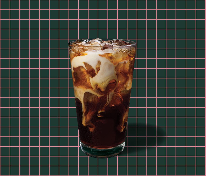Un café infusé à froid avec crème à la vanille sur un fond quadrillé.