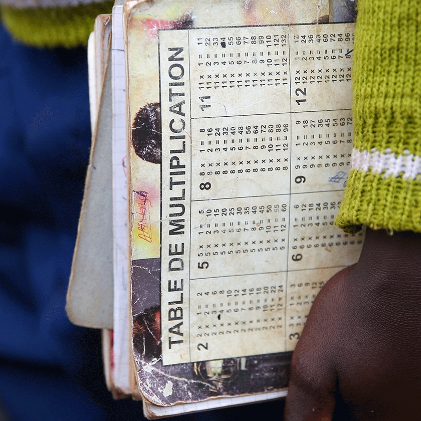 "Closeup of a child's arm and hand holding a notebook that reads ""Table de Multiplication"""