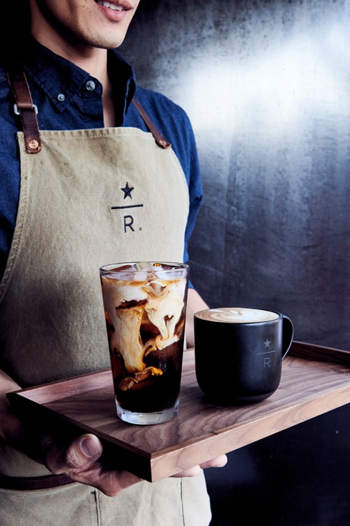 Closeup of person wearing Starbucks Reserve apron, placing a speared cherry on a cocktail