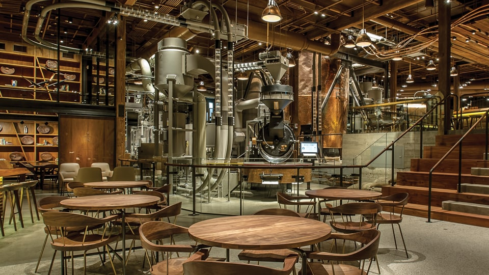 Interior of Seattle Roastery with coffee roasting machinery and chairs and tables