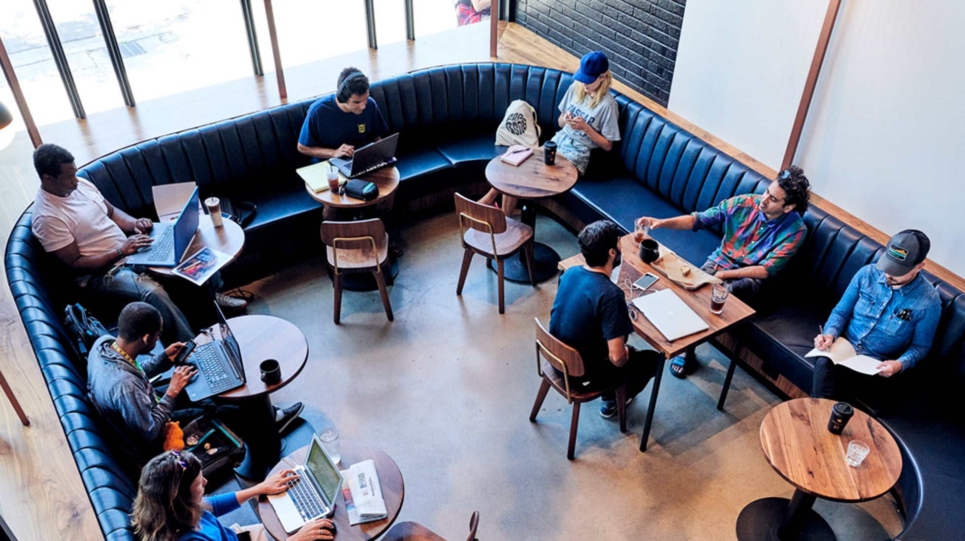 About a dozen people sitting individually at a café and working at laptops or in a notebook