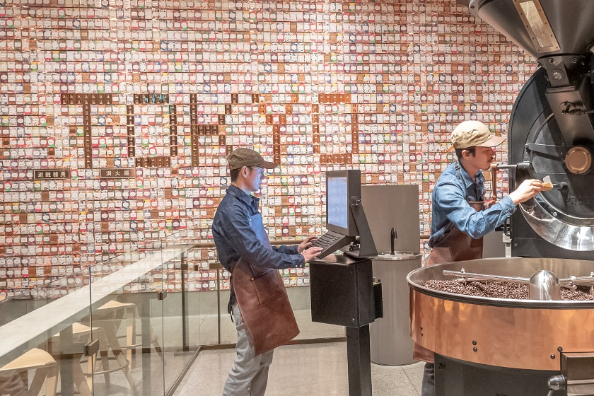 "Display of hundreds of colorful Starbucks Reserve coffee cards on a large wall, with ""TOKYO"" spelled out within, and coffee roasting equipment in foreground"