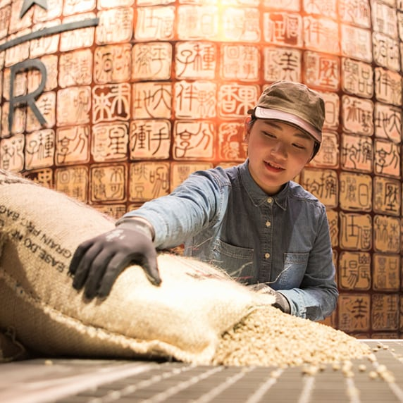 Starbucks Reserve employee handling burlap sack of unroasted coffee beans, in front of a background with Chinese characters