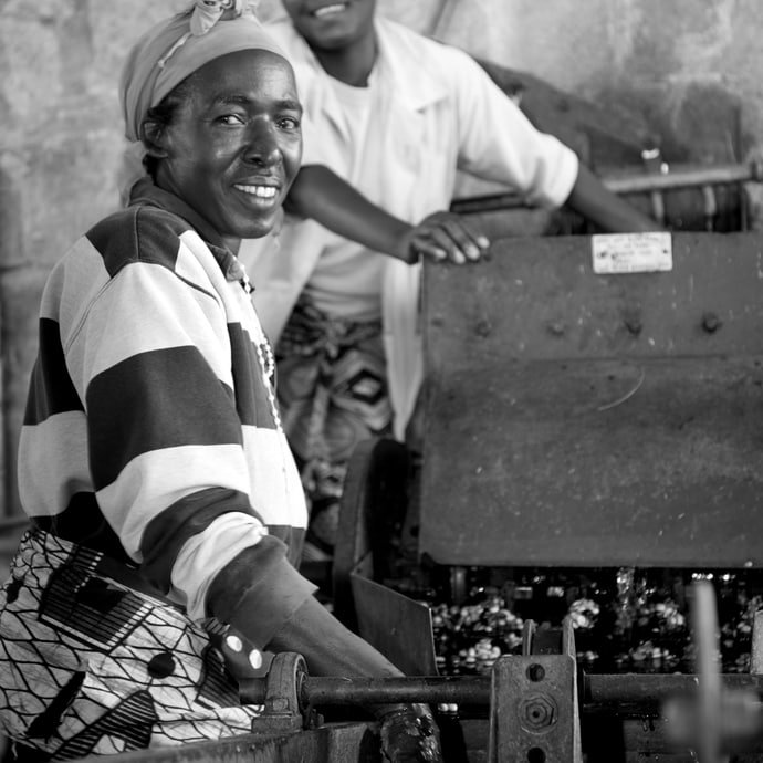 Black and white image of woman operating machinery and smiling at the camera