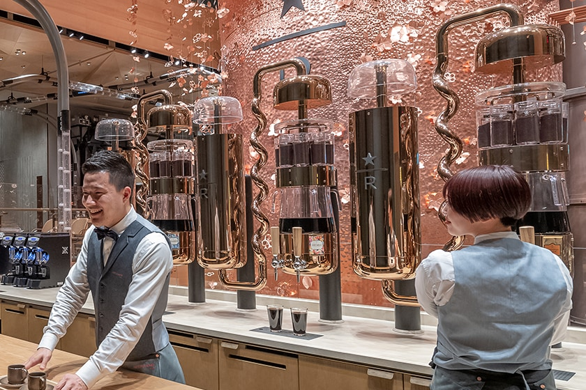 Two baristas in front of a row of cold brew silos which include intricate, curved pipes