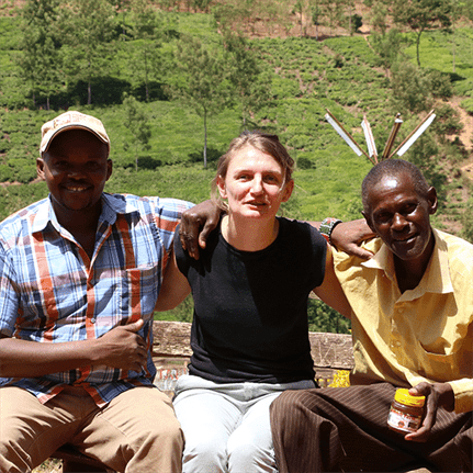 Three people, including one woman and two men, seated on a bench with arms around each other in front of a lush agricultural background