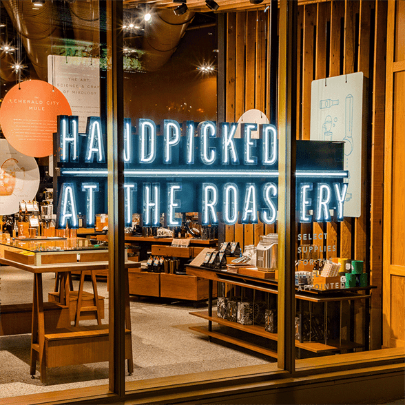 "Storefront with neon sign that reads ""Handpicked at the Roastery"" with merchandise in the background"