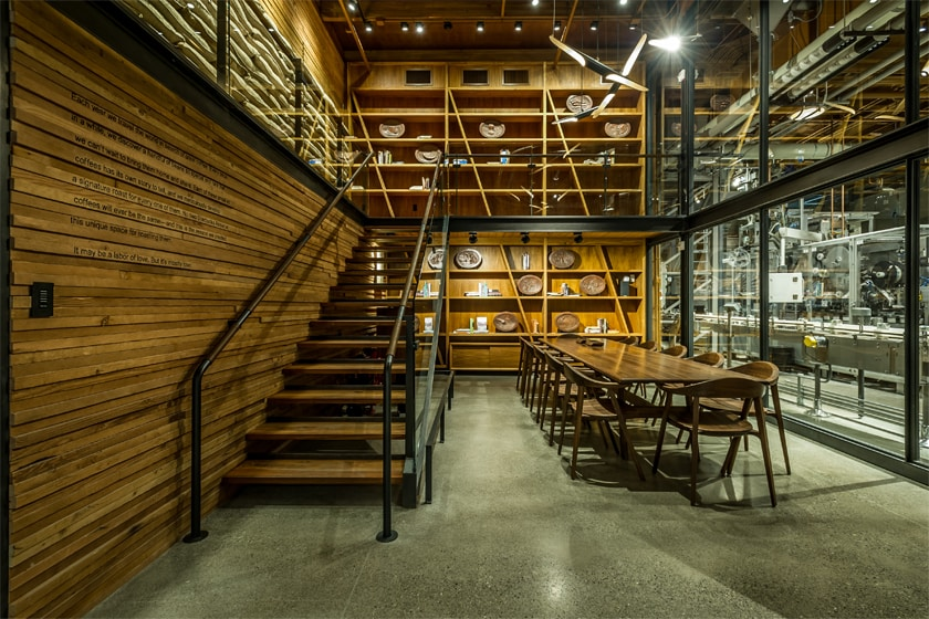 Large wood conference table and chairs, stairs leading to a lofted space, with bookshelves in the background.