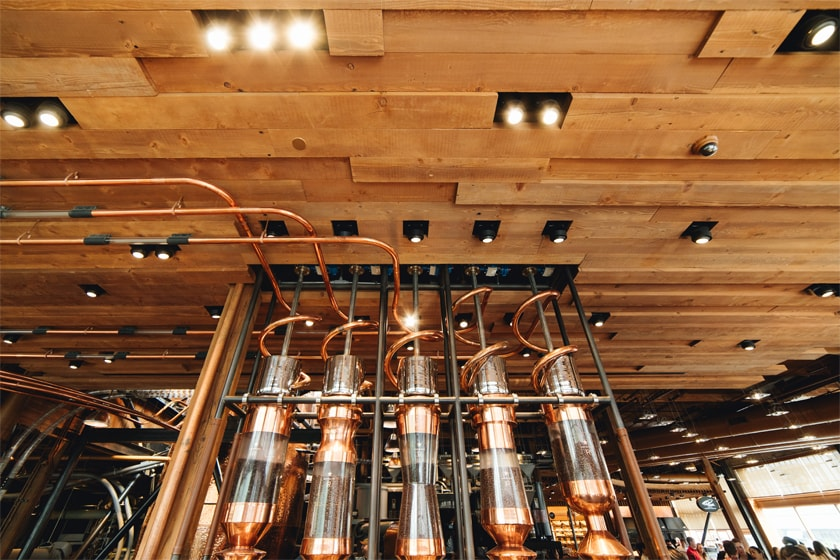 Large dispensing containers filled with coffee beans; copper tubes wind along the wood ceiling into these containers