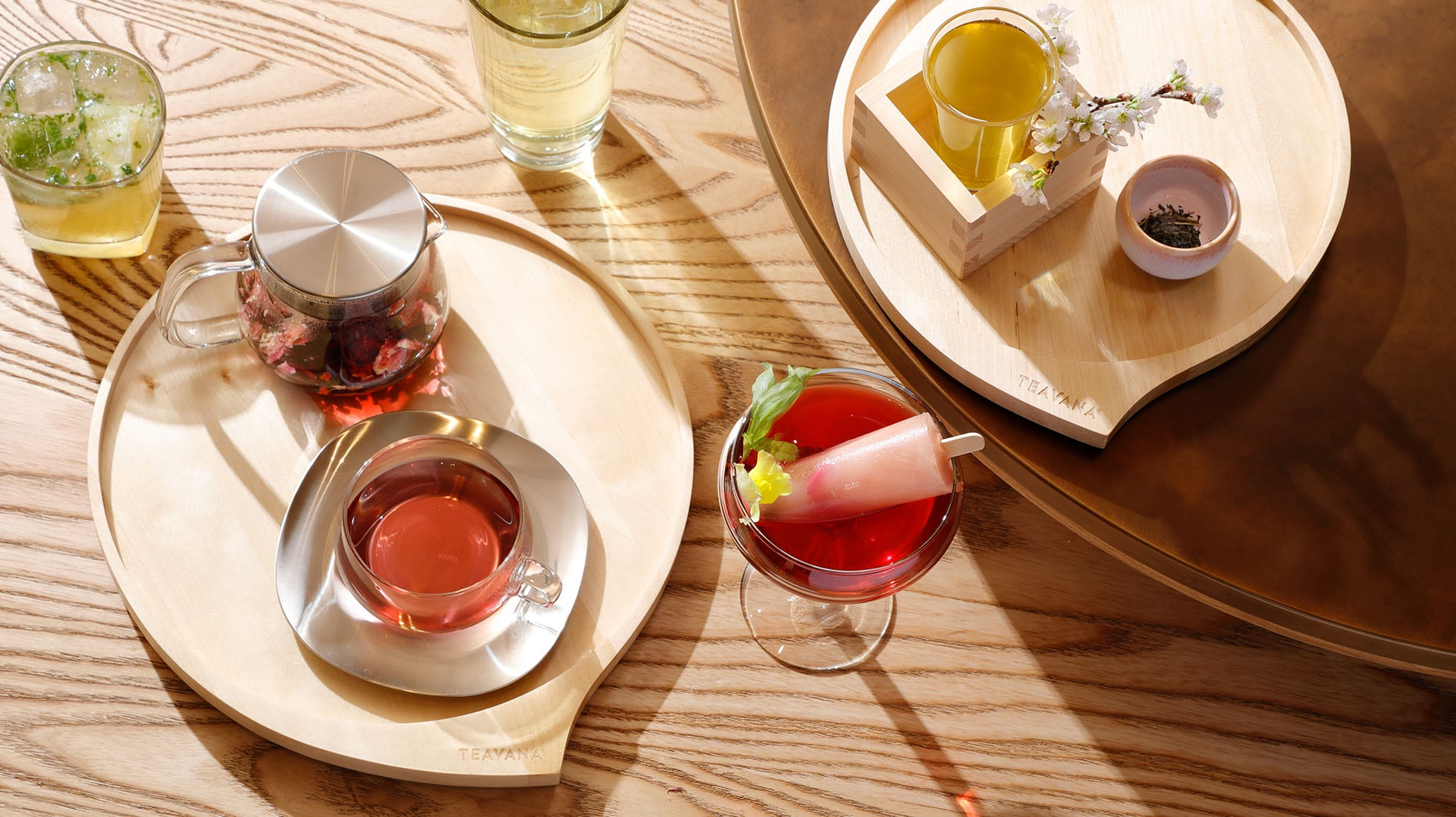 Image of a variety of hot and iced tea beverages on a wood table with two Teavana serving trays