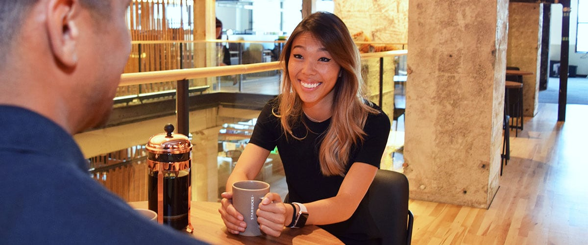 Woman seated at table holding coffee mug during interview