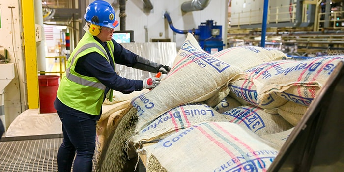 manufacturing partner wearing yellow safety vest, opening a burlap bag of coffee beans