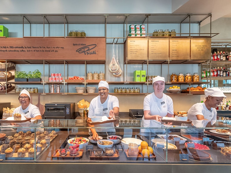 Four female Princi Bakery Partners smiling behind counter